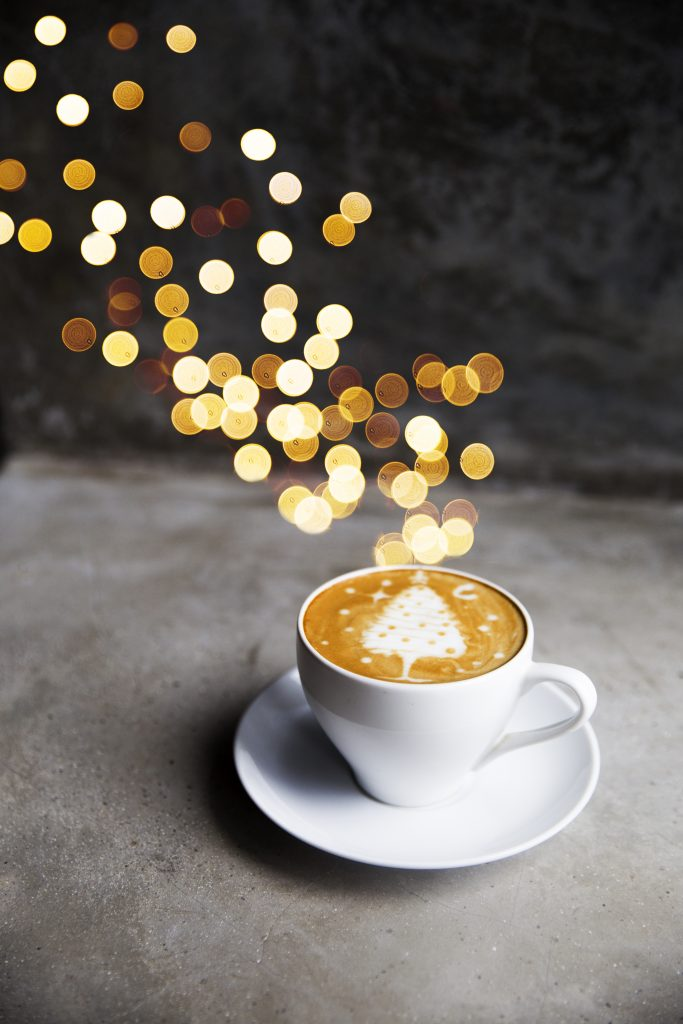 Tasty cappuccino with Christmas tree latte art with some blurred lights on grey concrete background. Holiday concept.